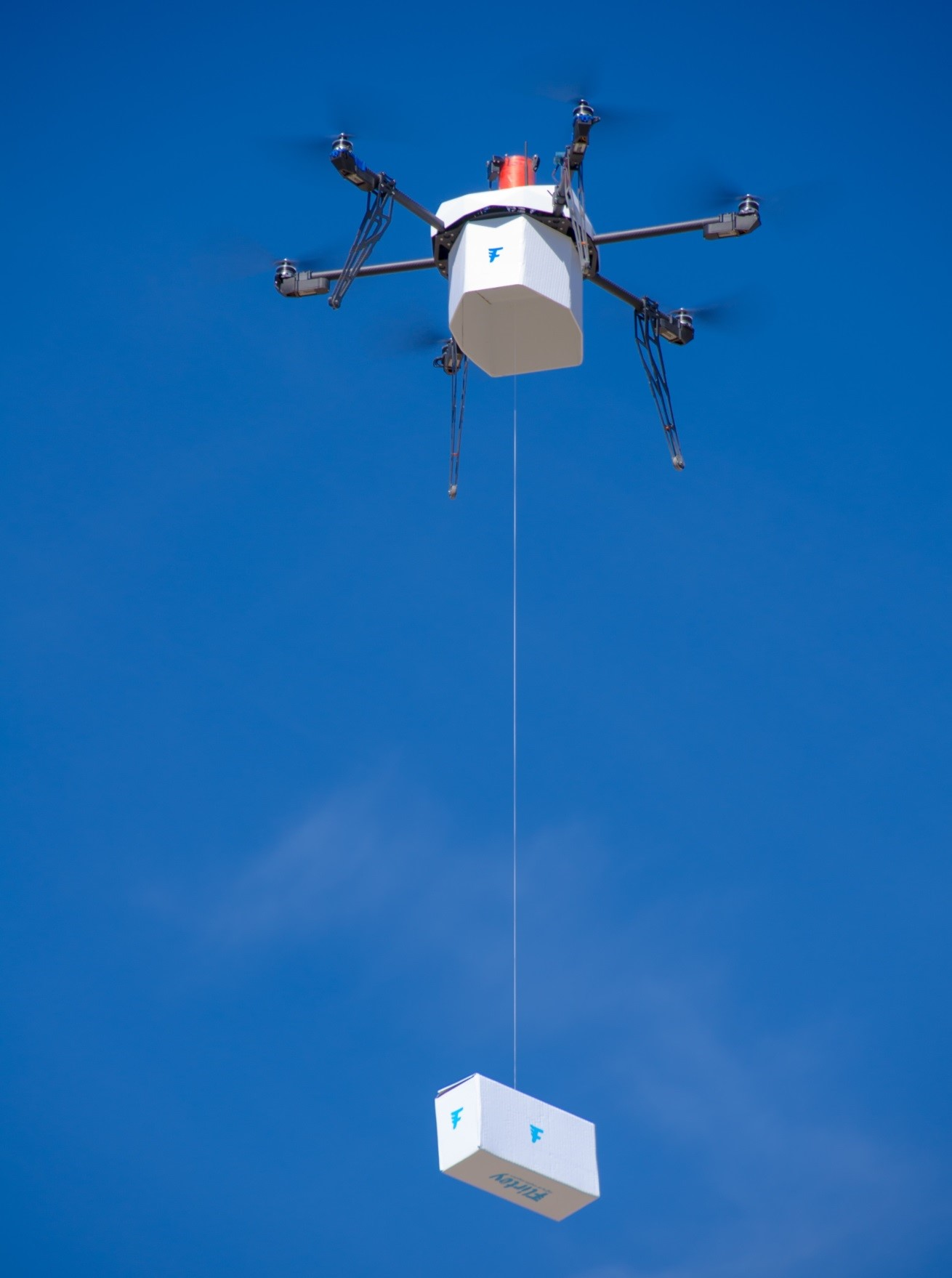 A box containing food, water and a first-aid kit is lowered from Flirtey's drone.